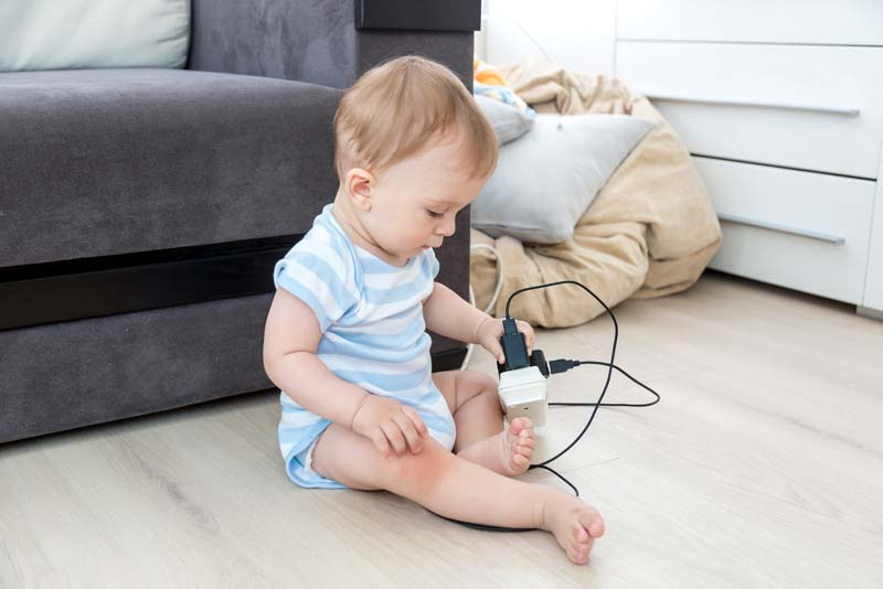 Baby boy sitting alone and playing with electrical cables