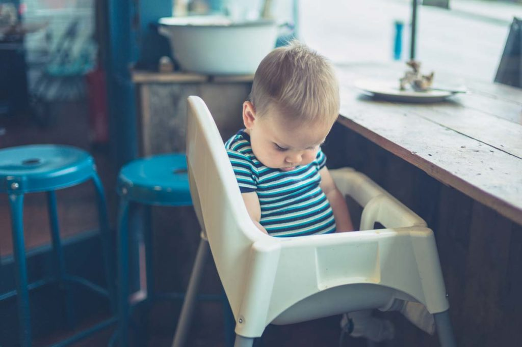 Baby in high chair by the window