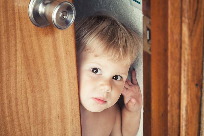 Little blond baby opens door and looks outside