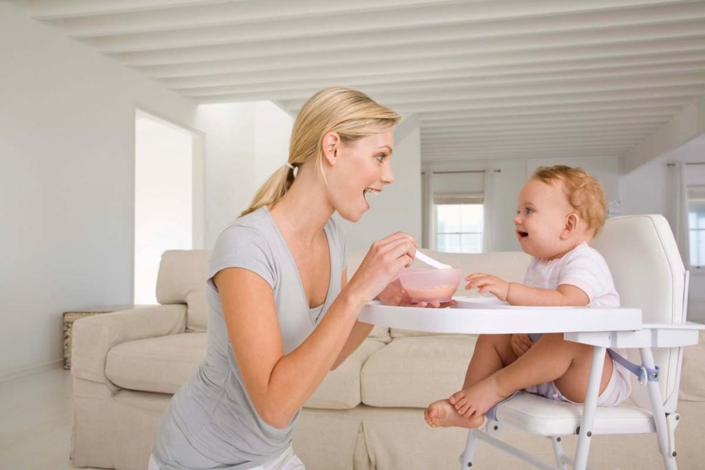 Mother feeding baby in high chair